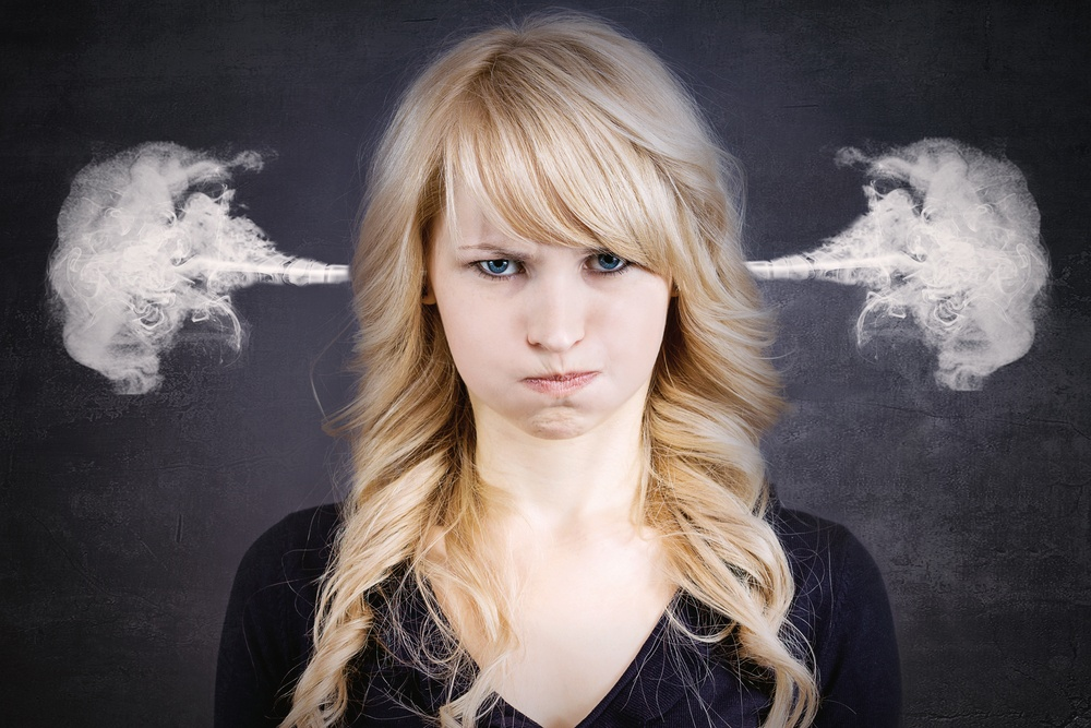 Closeup portrait of angry young woman, blowing steam coming out of ears, about to have nervous atomic breakdown, isolated black background. Negative human emotions facial expression feelings attitude.jpeg